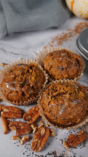 Muffins with pecans and poppy seeds next to them