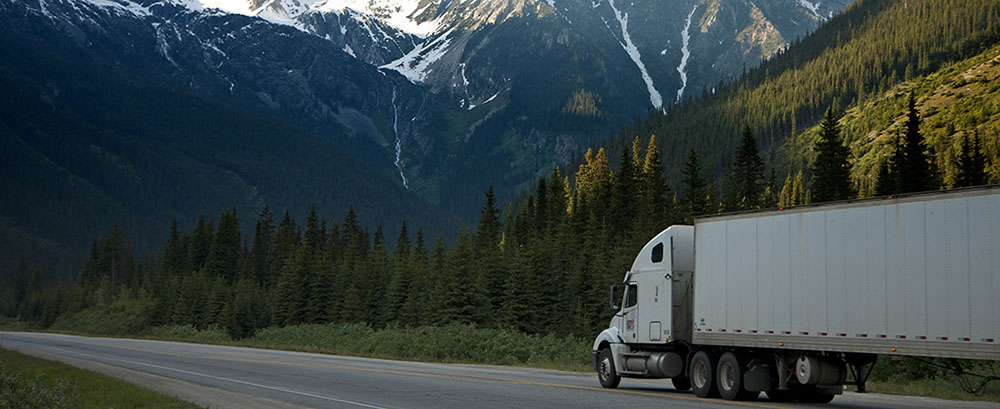 A delivery truck driving through mountains covered in pine trees