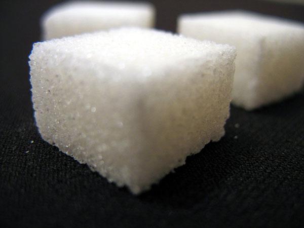 three sugar cubes sitting on a black table